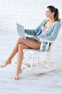 Beautiful woman working on laptop sitting in rocking chair at home