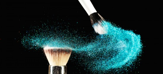 Art of visage.  Horizontal closeup photo of two professional black make-up brushes with blue powder isolated on black background with copy place