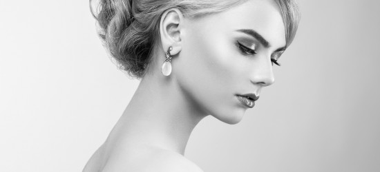 Portrait of beautiful sensual woman with elegant hairstyle.  Perfect makeup. Blonde girl. Fashion photo. Jewelry and dress. Black and white